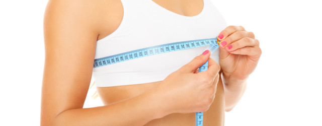 Women measures size of breast over white background